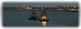 Sunset view of harbour with vessel and buoy lights.